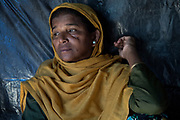 Rohingya refugee crisis. Foruda Khatun (50), survivor of the massacre at Tula Toli (Min Gyi village) in Myanmar inside her maske-shift shelter at the Balukhali refugee camp at Cox's Bazar District, Bangladesh - Photograph by David Dare Parker