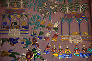 Luang Prabang, Laos. Scenes made of mirrored glass depicting Laotian daily life adorn the walls of the Buddhist Temple compound Wat Xieng Thong.