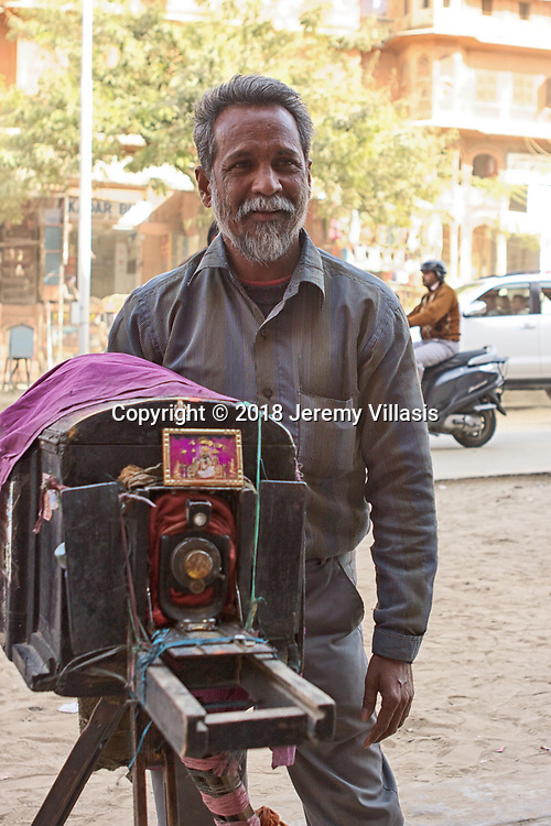 Tikam Chand's brother, Surendar, stands behind the vintage camera as he waits for the photograph to be developed.