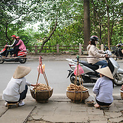 Two street vendors in Hanoi, Vietnam, sell yams and other roots on the side of a road as people on scooters race by.
