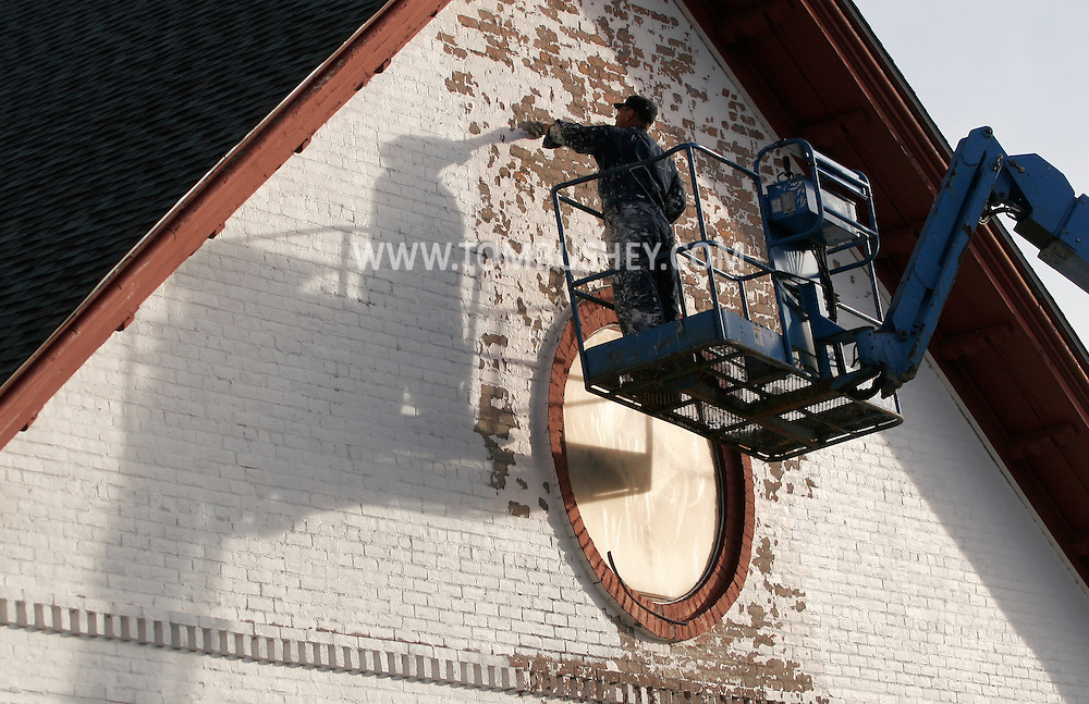 Middletown, N.Y. - A worker on a lift scrapes the front of the First Baptist Church to prepare the building for a new coat of paint on Oct. 24, 2007.