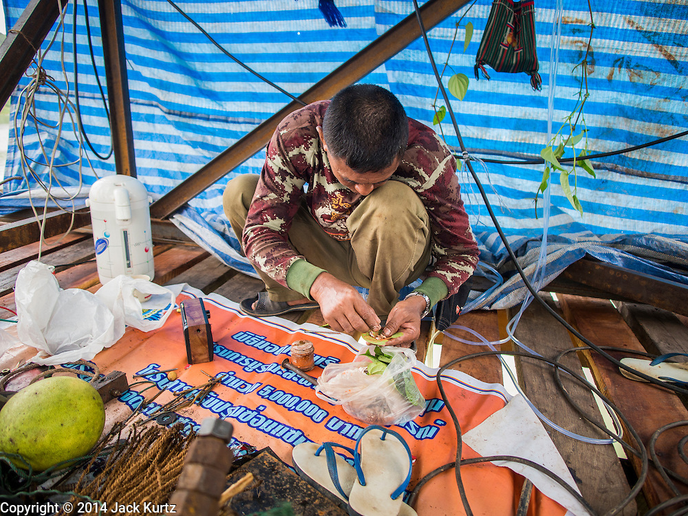 17 SEPTEMBER 2014 - SANGKHLA BURI, KANCHANABURI, THAILAND: A member of the Burmese Mon community in Sangkhla Buri makes some betel nut to chew while working on the repair of the Mon Bridge. The 2800 foot long (850 meters) Saphan Mon (Mon Bridge) spans the Song Kalia River. It is reportedly second longest wooden bridge in the world. The bridge was severely damaged during heavy rainfall in July 2013 when its 230 foot middle section  (70 meters) collapsed during flooding. Officially known as Uttamanusorn Bridge, the bridge has been used by people in Sangkhla Buri (also known as Sangkhlaburi) for 20 years. The bridge was was conceived by Luang Pho Uttama, the late abbot of of Wat Wang Wiwekaram, and was built by hand by Mon refugees from Myanmar (then Burma). The wooden bridge is one of the leading tourist attractions in Kanchanaburi province. The loss of the bridge has hurt the economy of the Mon community opposite Sangkhla Buri. The repair has taken far longer than expected. Thai Prime Minister General Prayuth Chan-ocha ordered an engineer unit of the Royal Thai Army to help the local Mon population repair the bridge. Local people said they hope the bridge is repaired by the end November, which is when the tourist season starts.    PHOTO BY JACK KURTZ
