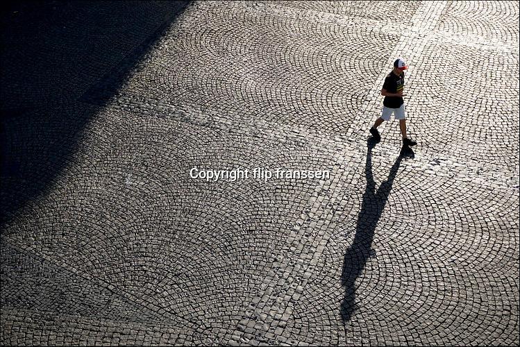 Nederland, Groningen, 20-8-2016Plein waar mensen, een man, onherkenbaar met hoog contrast in tegenlicht en met een langgerekte schaduw overheen lopen . Hij cheched zijn gsmFoto: Flip Franssen