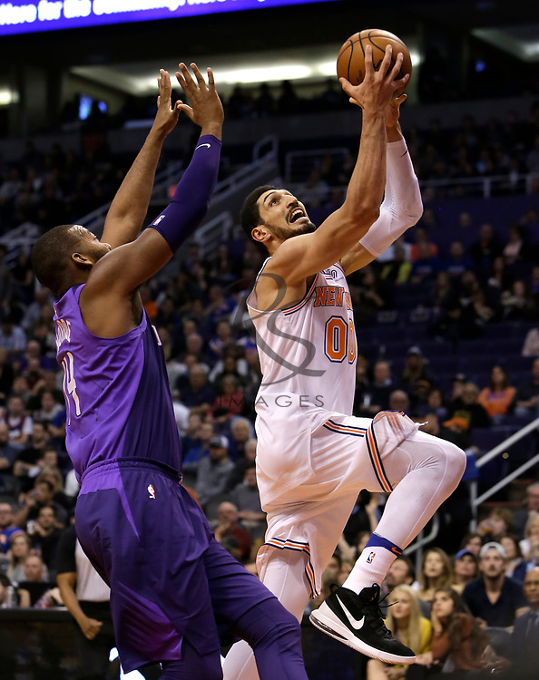 New York Knicks center Enes Kanter (00) drives past Phoenix Suns center Greg Monroe in the first half during an NBA basketball game, Friday, Jan. 26, 2018, in Phoenix. (AP Photo/Rick Scuteri)