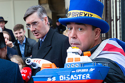 Steve Bray of SODEM, Stand of Defiance European Movement holds his boat the SS Disaster as pro-Brexit MP Jacob Rees-Mogg addresses the media outside the Houses of Parliament. London, January 15 2019.