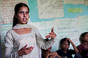 Bhawani Regmi (grey/pink), 16, talks about child marriage and the importance of family planning at a club meeting at the Kishuri Sachetana Child Club in their activity center in Thahuri Tole, Chhinchu, Surkhet district, Western Nepal, on 1st July 2012. Bhawani's ambition is to be a doctor. 16-year-old Bhawani Regmi (in grey/pink) who is the president of the district level child forum, 11-year-old  Sarawati Regmi (in white), and 10-year-old Ganga Regmi (in pink) are daughters of pandit (Hindu priest) Dharma Raj Regmi who is one of the 3 priests who have agreed to stop solemnizing child marriages. These Child Clubs, supported by the government, Save the Children and their local partner NGO Safer Society, advocate for child rights and against child marriages and use peer support and education to end child marriages and raise awareness. Photo by Suzanne Lee for Save The Children UK