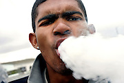 A youngster is smoking Mandrax (methaqualone) mixed with Marijuana in Heideveld, Cape Town, RSA.  Initially marketed as a sedative or sleeping tablet by the French pharmaceutical giant Roussell Laboratories, it turned out to be highly addictive and banned in 1977. Sold illegally in South Africa, it is smoked in conjunction with Marijuana and it is the most widely used drug in the Western Cape, sold at about 30 Rands (about 3 UK pounds) per tablet. It is crushed and smoked in pipes or bottlenecks. It makes the user feel relaxed, clam and peaceful and everything looks perfect, while turning aggressive when the effect is wearing off. It requires increased usage in order to achieve the same effects and depression feelings are not uncommon with use. According to the Cape Town Drug Counselling Centre (CTDCC) it is a really difficult habit to break in impoverished communities where young unemployed are left on their own with no government help or other activities apart from crime and gansgterism. Social injustice, weakened family links and a feeling of 'not-belonging' are also causes of problems upon the ?coloured? communities in South Africa.