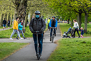 A masked man on an electric scooter crosses the common - Clapham Common is pretty quiet now as it is colder and Lambeth Council has taped up all the benches, put up signs and organised patrols by wardens. The 'lockdown' continues for the Coronavirus (Covid 19) outbreak in London.