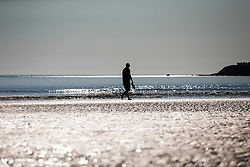© Licensed to London News Pictures. 19/07/2016. Scarborough Bay UK. Picture shows a man walking along the beach this morning in Scarborough. Temperature's are expected to reach a record high today.Photo credit: Andrew McCaren/LNP