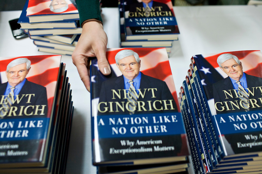 An aide places Republican presidential candidate Newt Gingrich's book on display before he addressed the Polk County Republican Party's Robb Kelley Victory Club dinner on Thursday, December 1, 2011 in Johnston, IA.