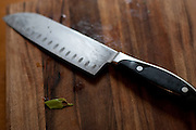 Black chef's knife photographed on a wooden cutting board.