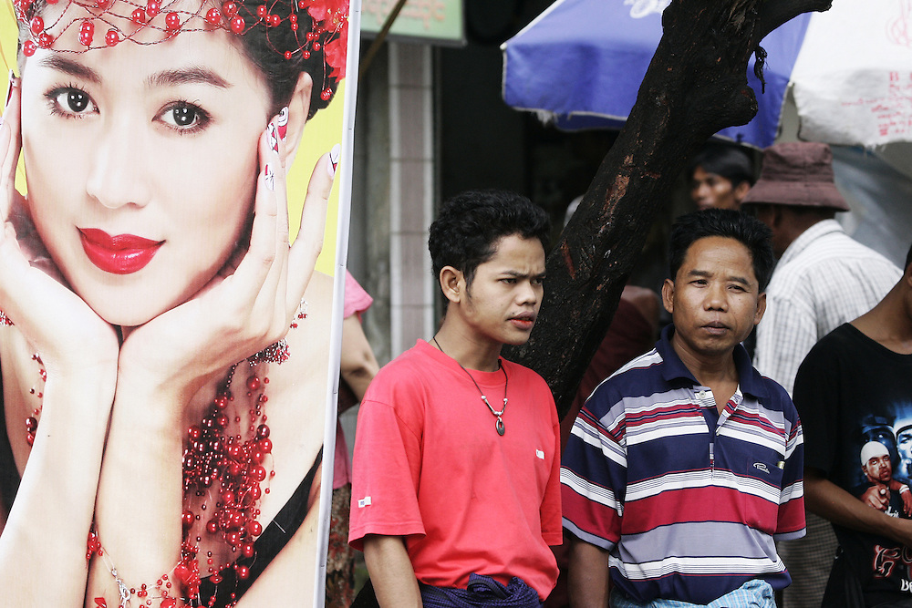 Burmese men stands next to a movie poster in downtown Rangoon, Burma.