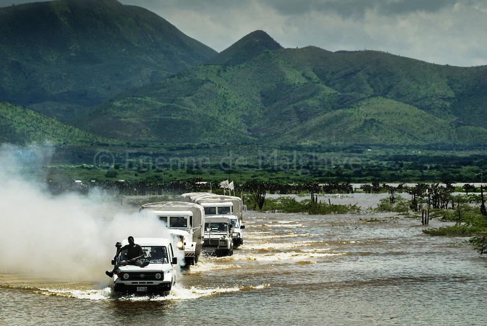 Avoiding invisible side ditches on a waist deep flooded road, a Red Cross relief convoy carefully arrives in Gonaives, an Haitian city ravaged with torrential rainfall from hurricane Jeanne. The convoy will be taken over by an armed escort of UN Minusta troops as aid trucks are otherwise systematically looted by gangs.  25 September 2004.