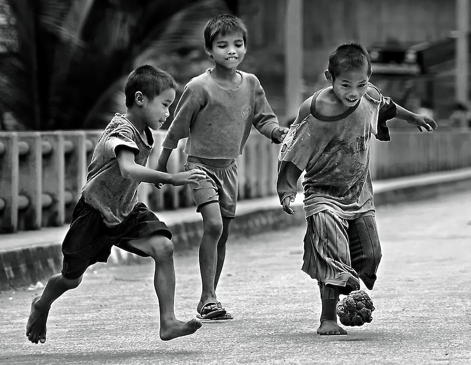Boys enjoy a football matchon a bridge in Luang Prabang, Laos using a home made rag ball.