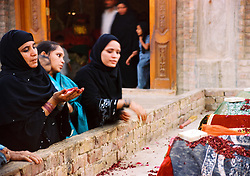 Pakistan, Sehwan Sharif, 2004. Supplicants throw rose petals on the symbolic graves of famous Sufi figures near the main shrine building.