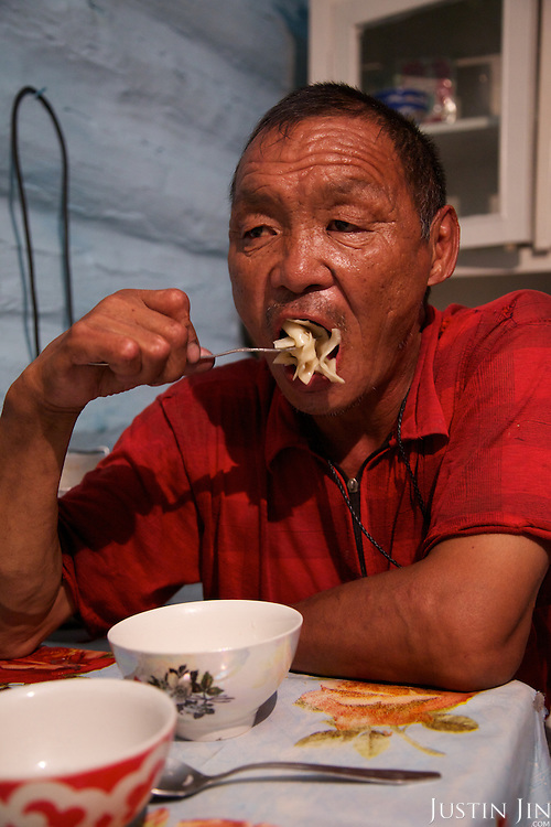 A farm worker at the Natpiool family eats at their home in Chodura, in the taiga in Tuva Republic, Russia
