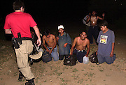 A group of undocumented migrants from Mexico, who crossed the border illegally, surrenders to a BORSTAR agent at Little Tucson in the heat of summer in the Sonoran Desert on the Tohono O'odam Nation in Arizona, USA.  The group reported leaving behind the body of an uncle who died from dehydration and heat exposure about a mile up the road and another relative who was ill.  Agents were in the area searching for another man who was ill and left behind by a different group of border crossers.  BORSTAR agents are part of a search and rescue unit.