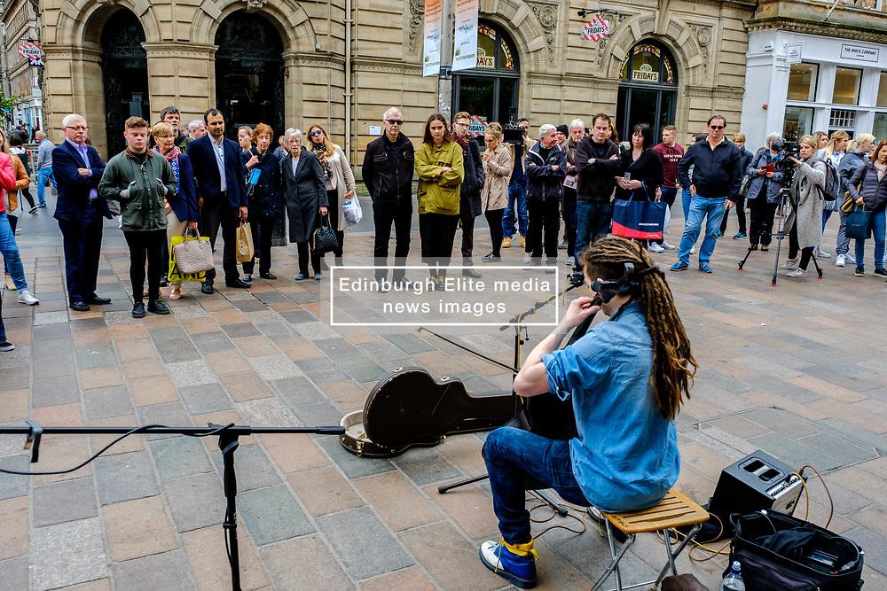Paisley born cellist/singer/songwriter CALUM INGRAM playing cello in Buchanan Street Glasgow while being filmed for a documentary. Record Producer Tony Visconti (Mark Bolan, Thin Lizzy, Morrisey, David Bowie) looks on (C - dark glasses).<br /> <br /> (c) Andrew Wilson | Edinburgh Elite media