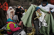 Refugees from Afghanistan and Syria are greeted by volunteers providing thermal blankets after they landed by rubber boats on the shores of Lesbos near Skala Sikaminias, Greece on 02 January, 2016. Lesbos, the Greek vacation island in the Aegean Sea between Turkey and Greece, faces massive refugee flows from the Middle East countries.