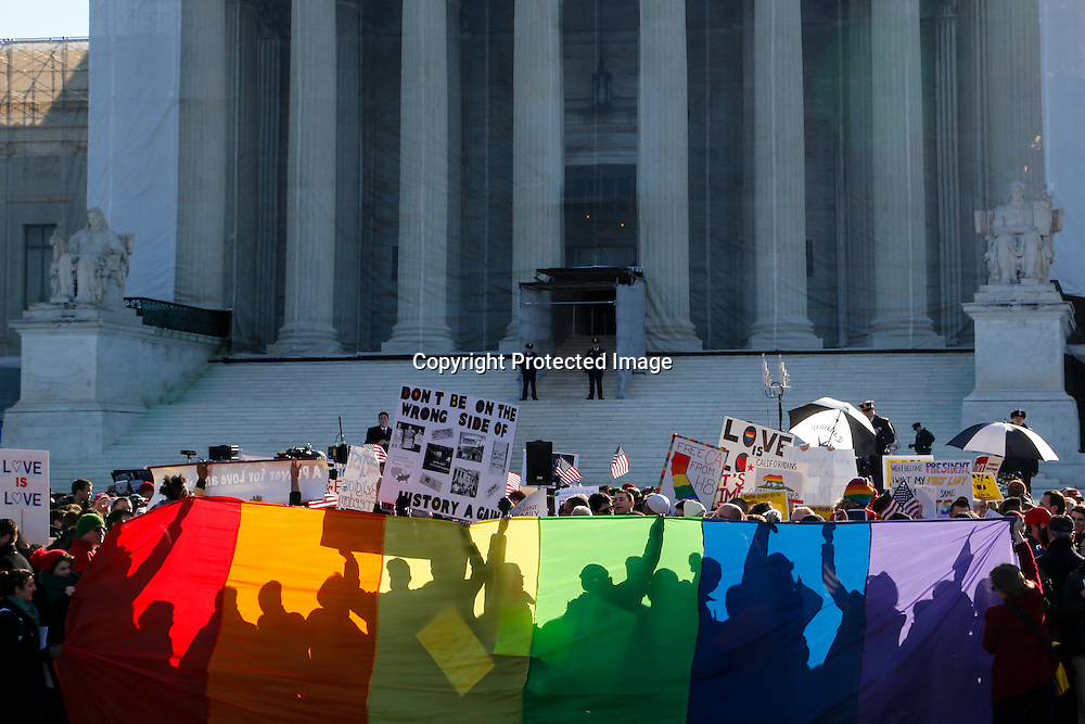 Anti-Proposition 8 protesters throw their shadows on a rainbow banner in front of the U.S. Supreme Court in Washington.