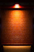 Light shining on a textured wooden stained wall in a bar