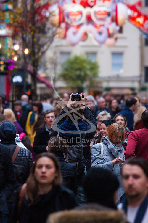 """London, December 23rd 2014. Dubbed by retailers as the """"Golden Hour"""" thousands of shoppers use their lunch hour to do some last minute Christmas shopping in London's West End. PICTURED: A man takes a high level shot of the crowds on Carnaby Street."""