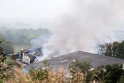 Firefighters are still on the scene of a large blaze involving a single storey warehouse on a Sheffield Industrial Estate, just off Station Road in Ecclesfield close to South Yorkshire Police Sub Divisional HQ and Chapeltown Academy. The fire started just after 9.30pm on Wednesday 3rd Sept and a number of loud explosions were heard during the course of the night. The fire which involved 2,000 tonnes of waste plastics has destroyed the building and caused serious damage to a car paint spraying unit close by.<br /> <br /> 4 September 2014<br /> <br /> Image © Paul David Drabble <br /> www.pauldaviddrabble.co.uk