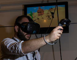 Scotland's first virtual reality arcade. E-VR opens on December 1 at Ocean Terminal, Edinburgh. It offers a variety of virtual reality  (VR) experiences and games. <br /> <br /> Pictured:   Piotr Pyrchala VR user showcasing an HTC Vive headset.