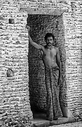 Man in doorway of coral and lime walled home.