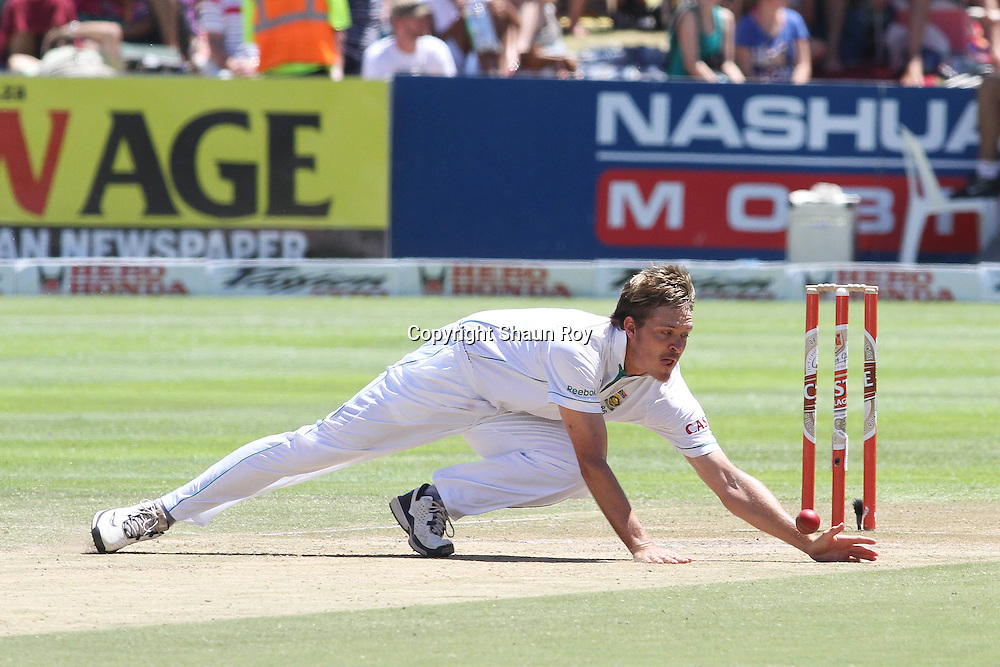 CAPE TOWN, SOUTH AFRICA - 4 January 2011, Paul Harris of South Africa makes a diving stop off his own bowling during day 3 of the 3rd Castle Test between South Africa and India held at Sahara Park Newlands Stadium in Cape Town, South Africa on the 4 January 2011 .Photo by: Shaun Roy