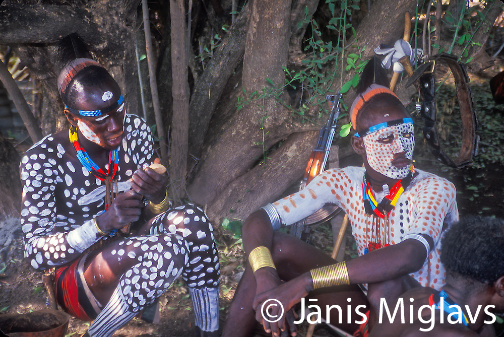 Africa, southern Ethiopia, Great Rift Valley, Omo River Valley. Warriors of the Karo tribe, which lives along the banks of the Omo River, paint their bodies in preparation for a ceremony.