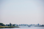 Bij Ameide vaart een vrachtschip over de Lek.<br /> <br /> Near Ameide a vessel is sailing on the river Lek.