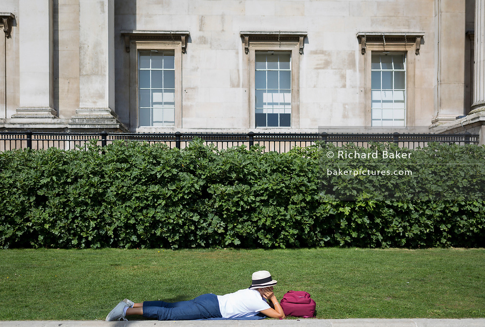 A tourist lies down next to grass outside the National Gallery, on 29th August 2019, in Trafalgar Square, London, England.