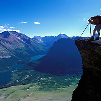 Photographer above Many Glacier Valley. Glacier National Park, Montana. Swiftcurrent and Josephine lakes below.