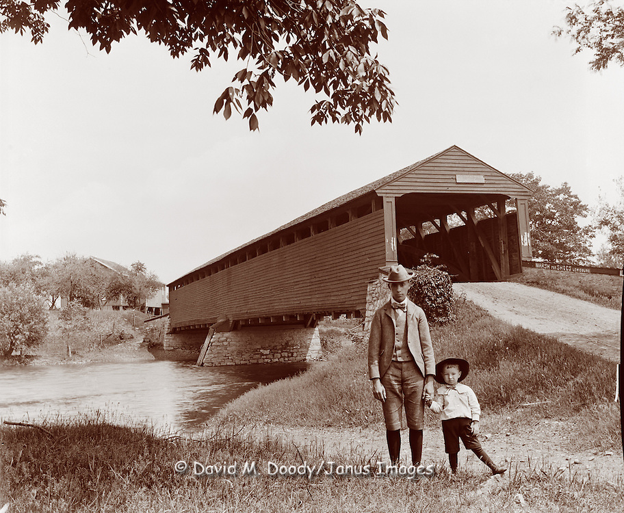 Vintage Photo: a well dressed little boy and man in front of a covered bridge, circa 1900 near Lewisburg Pennsylvania