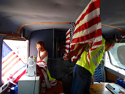 New York artist MARY MIHELIC and Philadelphia artist DAVID GLEESEN drove a former Trump-Campaign bus turned art installation to the April 25, 2016 Trump rally. Inside the bus MARY MIHELIC is seen working on art project as she embroiders American Flags with phrases Trump said during his campaign. Trump-Supporters and anti-Trump protestors face each other outside a rally of the Republican candidate, held at the campus of West Chester University in West Chester, Pennsylvania a day ahead of the Pennsylvania Primary.