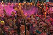 Devotees gather at the Krishna Temple of Shriji, during Lathmar Holi. Men from Barsana raid the town whilst being assaulted with coloured water sprayed from rooftops, they are beaten by Nandgaon's women with large sticks and smeared with Holi coloured powders in a counterpart festival to the one held in Barsana on the previous day. The spectacle is a riot of colour amidst frenzied celebrations.