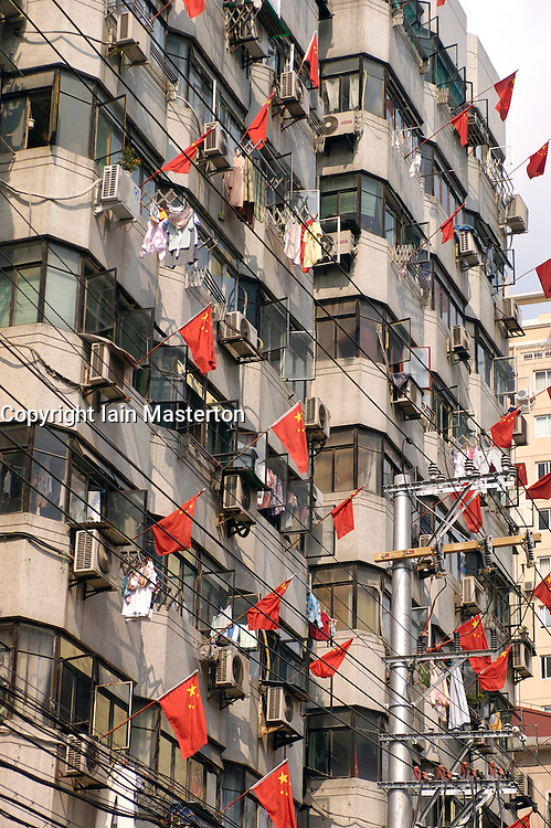 Many red Chinese flags flying from apartment building on National Day holiday in Shanghai China