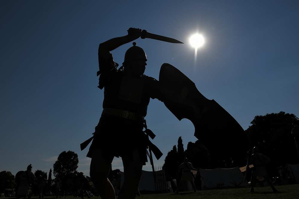 Aquileia, Italy - 17 June 2018: a Legionary with gladius sword, helmet and shield combats in silhouette during Tempora in Aquileia, ancient Roman historical re-enactment