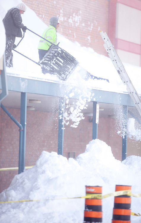 Workers clear snow from the roof at Northland Plaza in London, Ontario December 8, 2010. The region has been pummelled by snow squalls for 3 days with some areas receiving over 1.5 metres of snow.<br /> The Canadian Press/GEOFF ROBINS