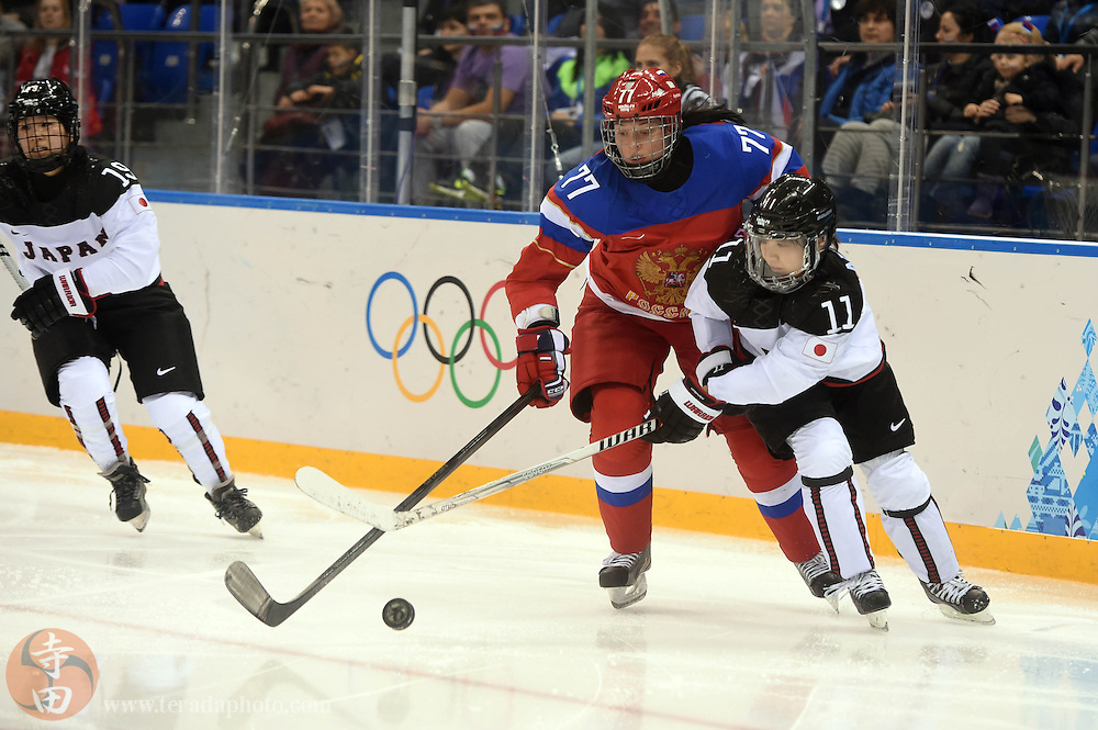 Feb 16, 2014; Sochi, RUSSIA; Russia defenseman Inna Dyubanok (77) battles fo the puck with Japan forwrad Yurie Adachi (11) in a women's ice hockey classifications round game during the Sochi 2014 Olympic Winter Games at Shayba Arena.