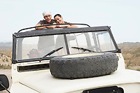 Couple standing side by side in stationary four wheel drive car in desert portrait