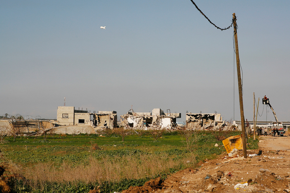 In the midst of their ongoing siege of the Gaza Strip, on 27 December Israel launched attacks by air, land and sea against the 1.5 million Palestinians of Gaza. The attacks, said to put an end to homemade rocket fire from armed groups in Gaza into Israel, left more than 1,300 Palestinians killed, the majority of whom were civilians including almost 450 children. Thousands of homes and businesses were also destroyed throughout the territory.///An Israeli surveillance balloon flies on the Gaza-Israel border overlooking destroyed Palestinian home in Beit Hanoun in the northern Gaza Strip.