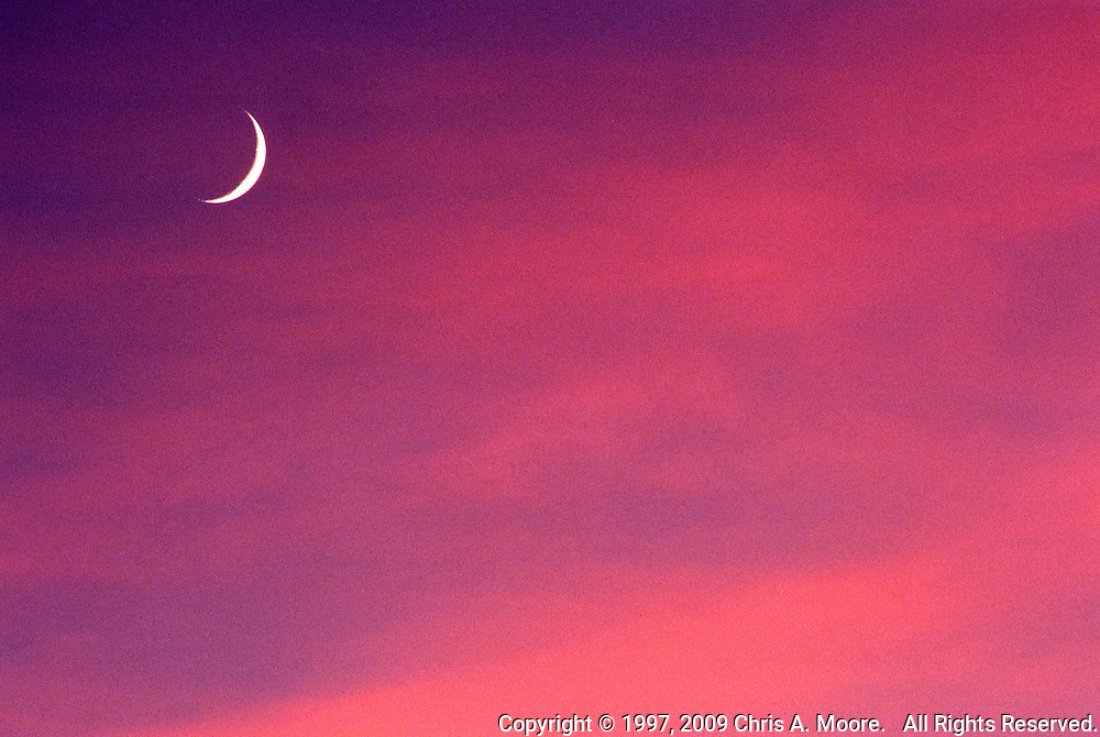 A Crescent Moon shines though orange and magenta alto stratus clouds at sunset in Denver, Colorado, October 1997.