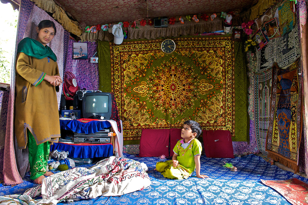 A mother and her child show the highly decorated living room of their houseboat floating on the Dal Lake.
