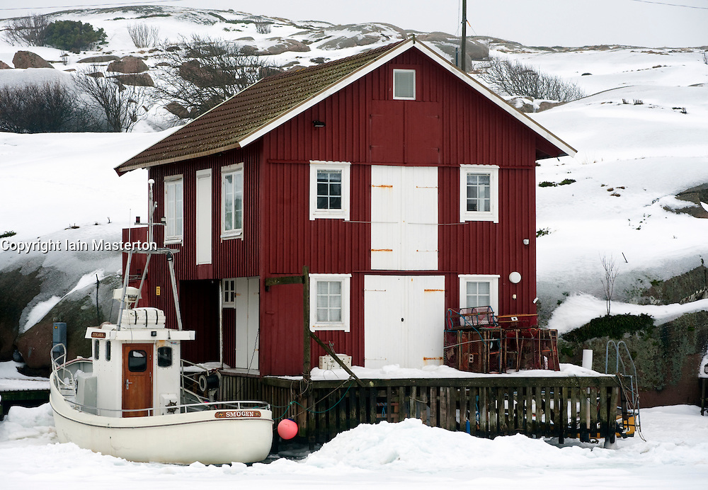 Boat and red boathouse in traditional fishing village of Smogen during winter after snow on Bohuslan coast in Sweden