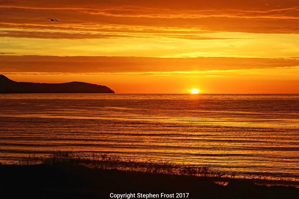 The sun rises behind a distant oil well on an early mid-summer dawn over the Moray Firth, from the Black Isle, near Inverness, Scotland.