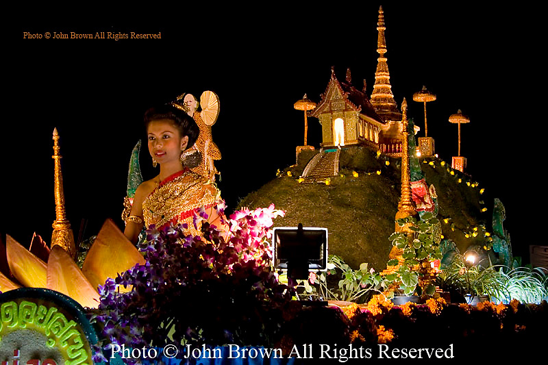 A traditionally costumed Thai woman rides on a passing float during the annual Loi Krathong Festival parade in Chiang Mai, Thailand.