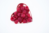 Raspberries in a red heart-shaped cookie cutter.