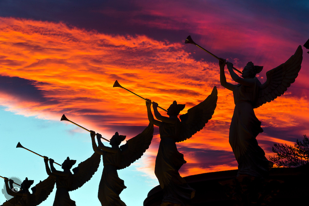 Sunset bathes the statues of angels blowing trumpets at Caesars Palace.